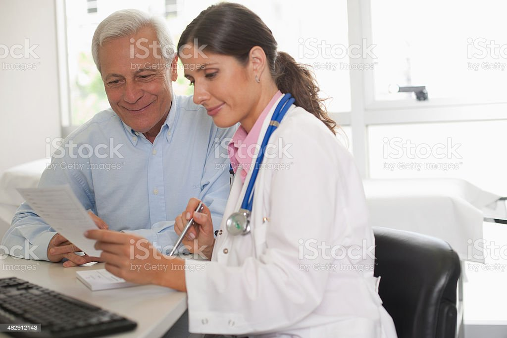 Doctor sitting in office with patient talking and holding paper stock photo