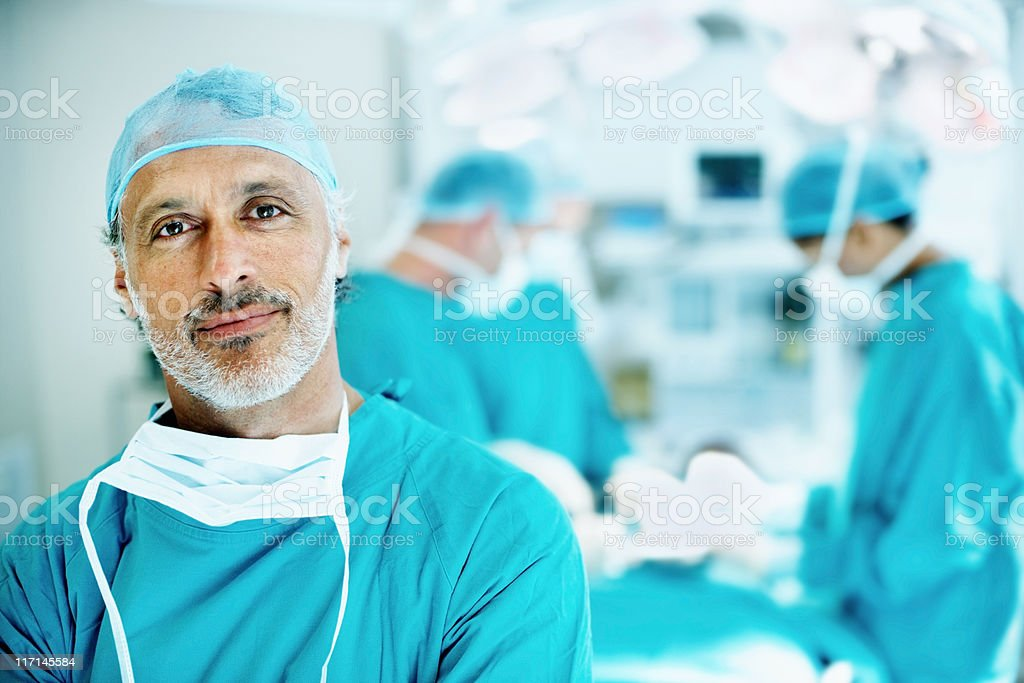 Doctor smiling in operating theater stock photo