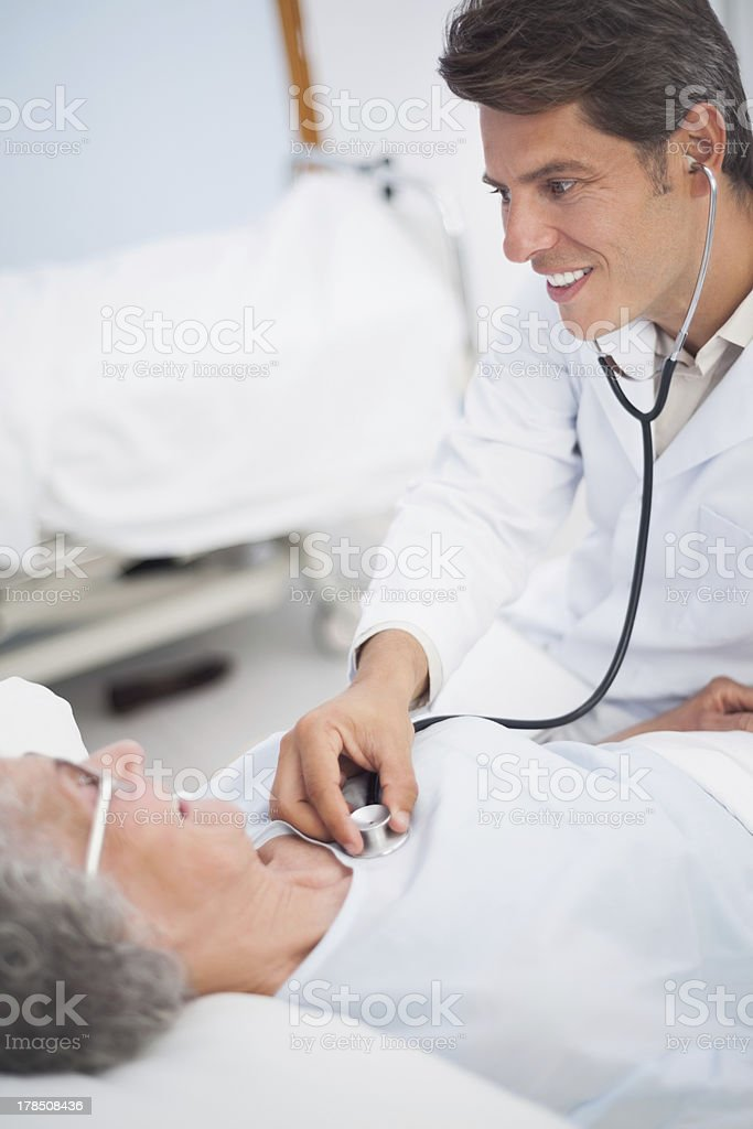 Doctor smiling while auscultating a patient royalty-free stock photo