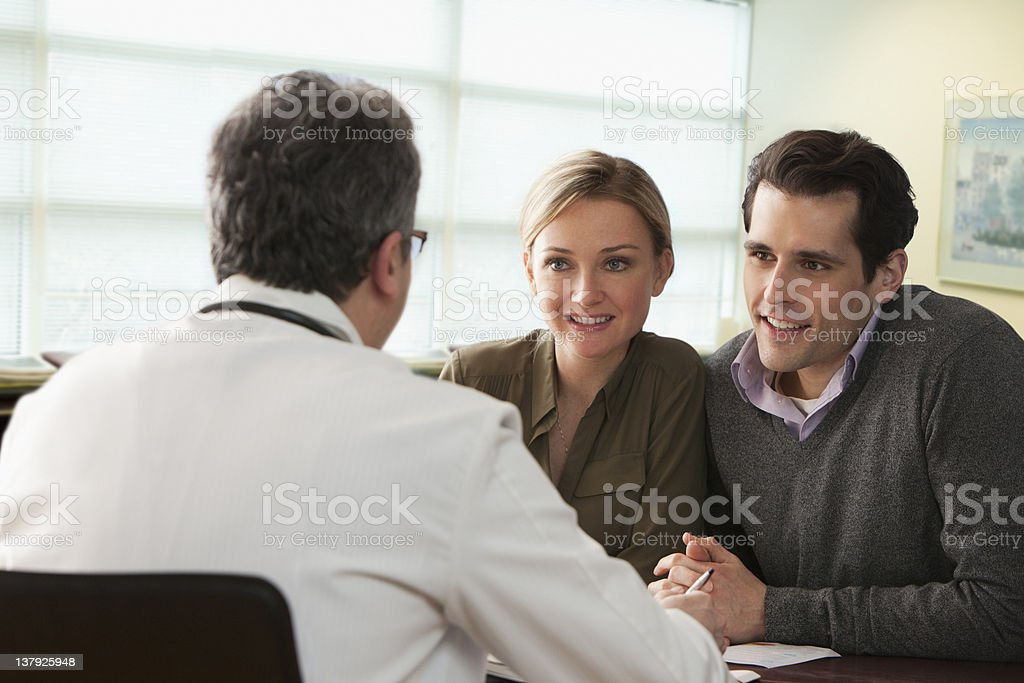 Doctor speaking to young couple royalty-free stock photo