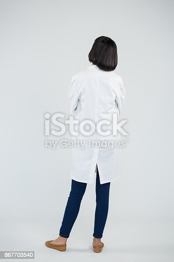 istock Doctor standing against white background 867703540