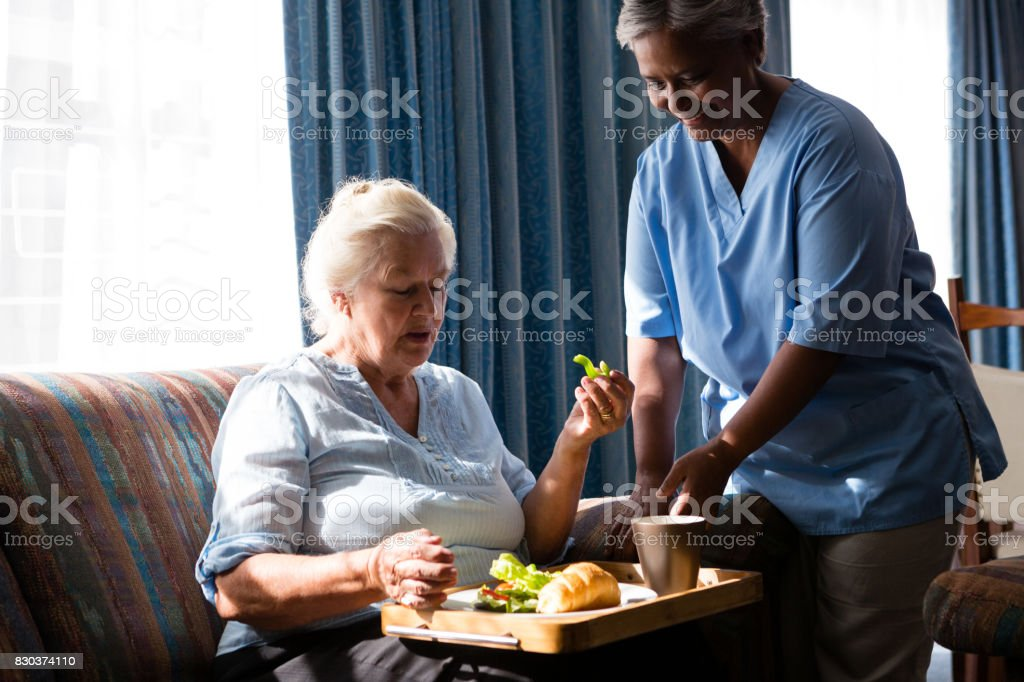 Doctor standing by senior woman eating food at table stock photo