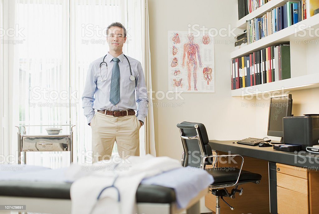 Doctor standing in doctors office stock photo