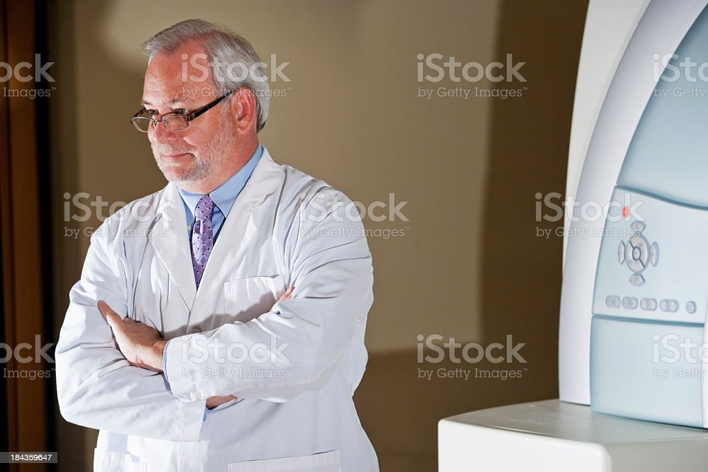 Doctor standing next to MRI scanner stock photo