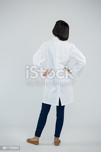 istock Doctor standing with hands on hip against white background 867703552