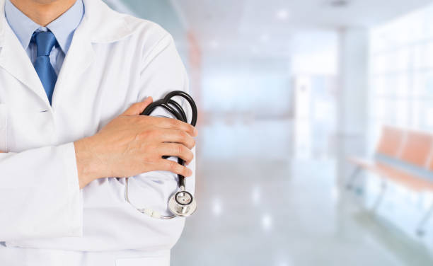doctor standing with his arms folded inside stock photo