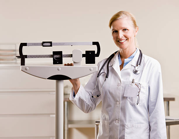 Doctor standing with weighing scales stock photo