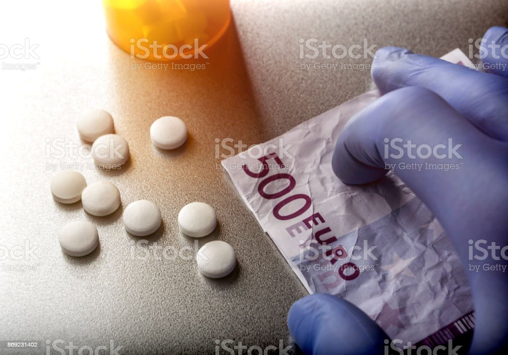 Doctor supports in its hand a ticket for 500 euros in exchange for some white pills stock photo
