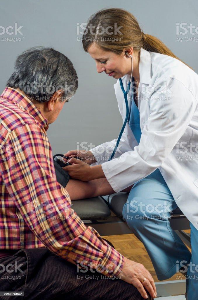 Doctor takes senior man's arterial blood pressure. Health care stock photo