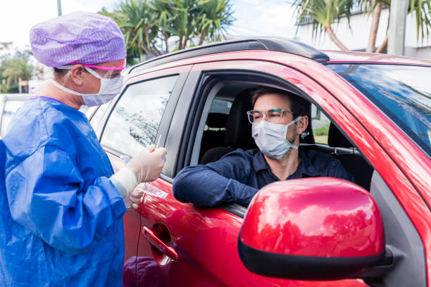 un médico que toma un hisopo nasal de un conductor - covid 19 fotografías e imágenes de stock