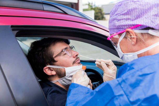 A doctor taking a nasal swab from a driver A doctor in a protective suit taking a nasal swab from a person to test for possible coronavirus infection testing kit stock pictures, royalty-free photos & images