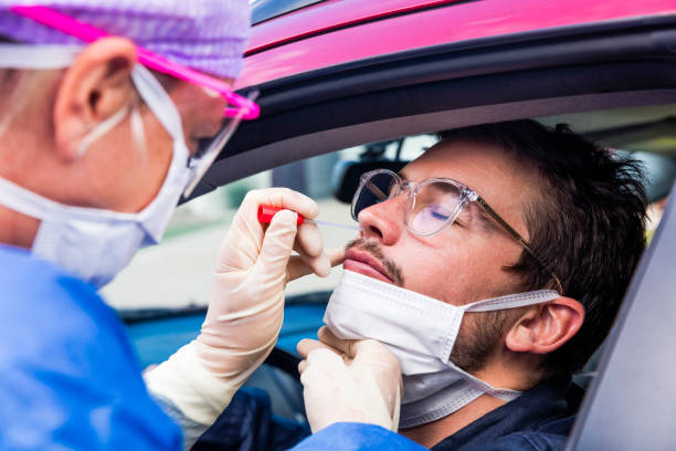 A doctor taking a nasal swab from a driver stock photo