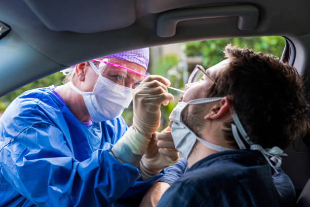 A doctor taking a nasal swab from a driver A doctor in a protective suit taking a nasal swab from a person to test for possible coronavirus infection cotton stock pictures, royalty-free photos & images