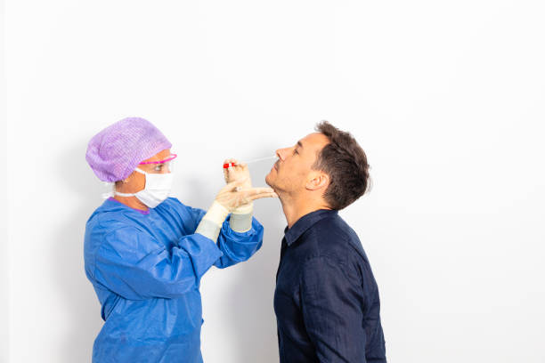 A doctor taking a nasal swab A doctor in a protective suit taking a nasal swab from a person to test for possible coronavirus infection testing kit stock pictures, royalty-free photos & images