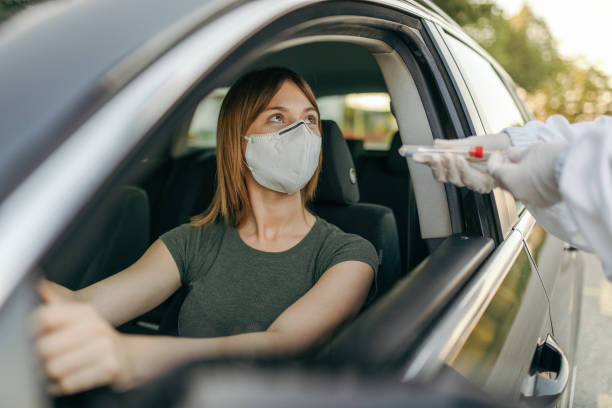 A doctor taking a swab from a car driver in front of public building stock photo