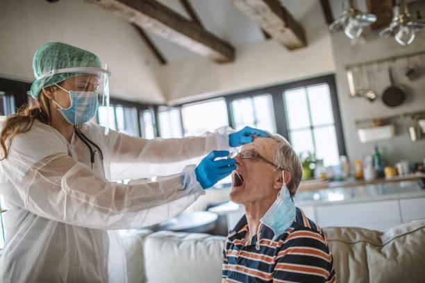 Arzt unter nimmt einen Kehlkopftest von einem Senior zu Hause – Foto