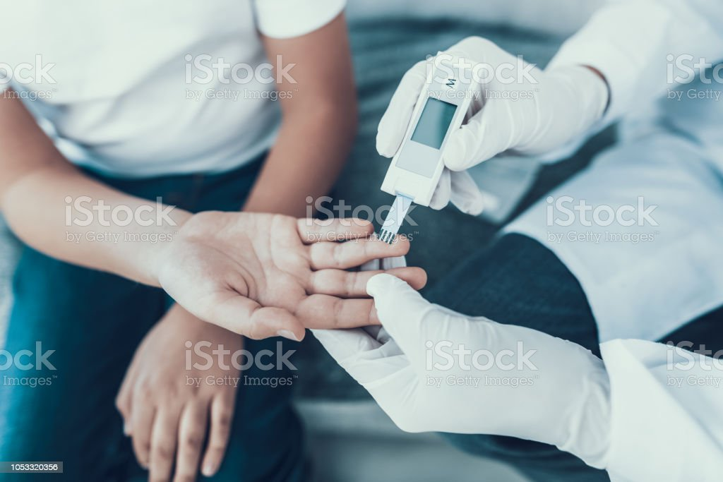 Doctor Taking Blood Sample from Boy's Finger. Doctor Taking Blood Sample from Boy's Finger. Diabetes Concept. Sugar in Blood. Healthcare Concept. Young Man in Uniform. White Coat. Medical Equipment. Boy in Clinic. Glucometer in Hand. Adult Stock Photo