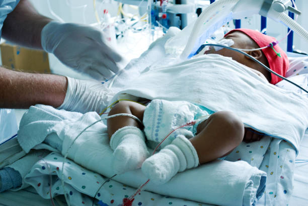 A doctor taking care of a critically sick baby hooked on a ventilator in a hospital paediatric intensive care ward A doctor taking care of a critically sick baby hooked on a ventilator in a hospital paediatric intensive care ward neonatal intensive care unit stock pictures, royalty-free photos & images