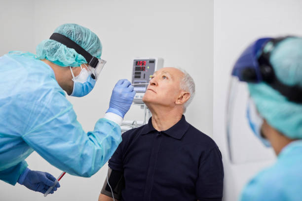Doctor Taking Coronavirus Sample From Male's Nose, PCR. Doctor taking coronavirus sample from male patient's nose. Frontline worker is in protective workwear. They are at hospital during epidemic. scientific experiment stock pictures, royalty-free photos & images