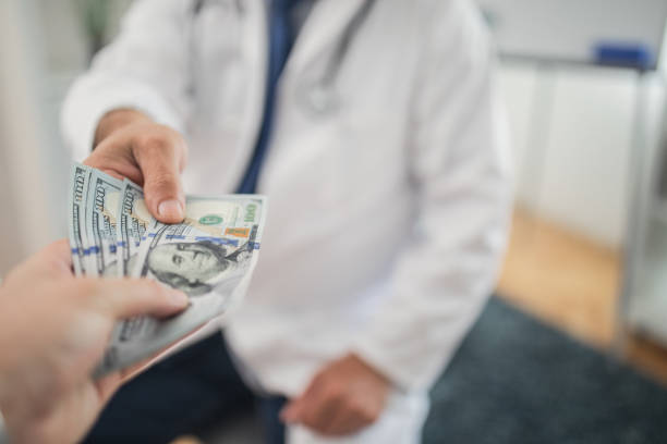 doctor taking money from patient - money bills and currency stock pictures, royalty-free photos & images