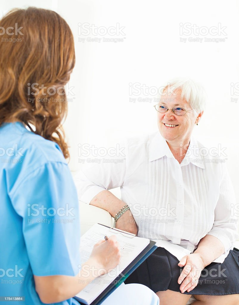 Doctor Taking Notes from Senior Woman patient. stock photo