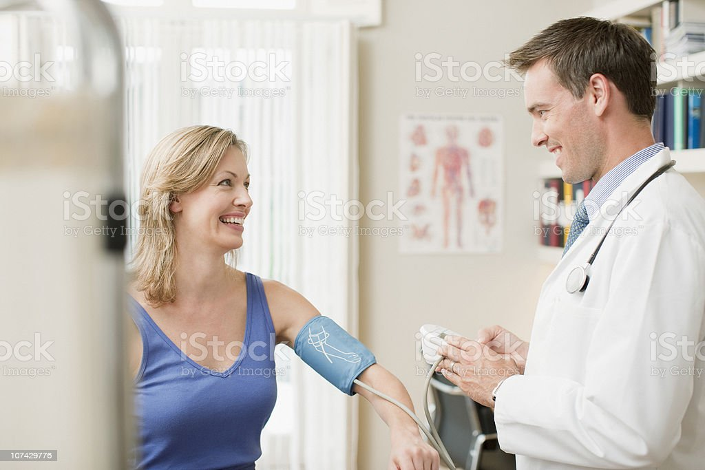 Doctor taking patients blood pressure in doctors office stock photo