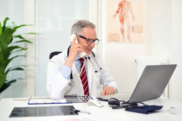 Doctor talking on the phone in his studio stock photo