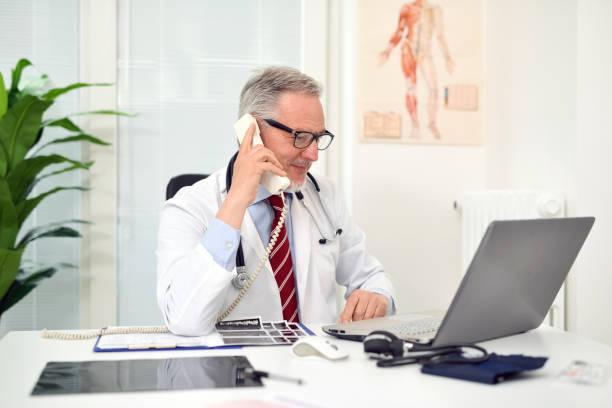 Arzt am Telefon in seinem Atelier – Foto