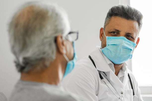 Doctor talking to a senior patient at home stock photo