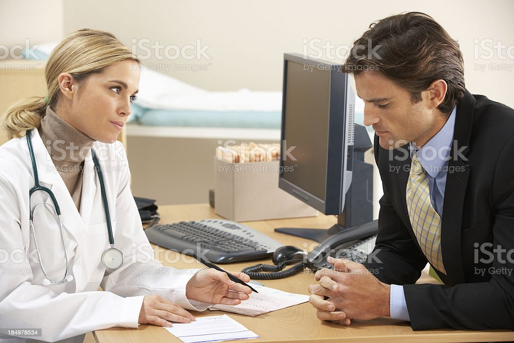 Doctor talking to businessman patient royalty-free stock photo