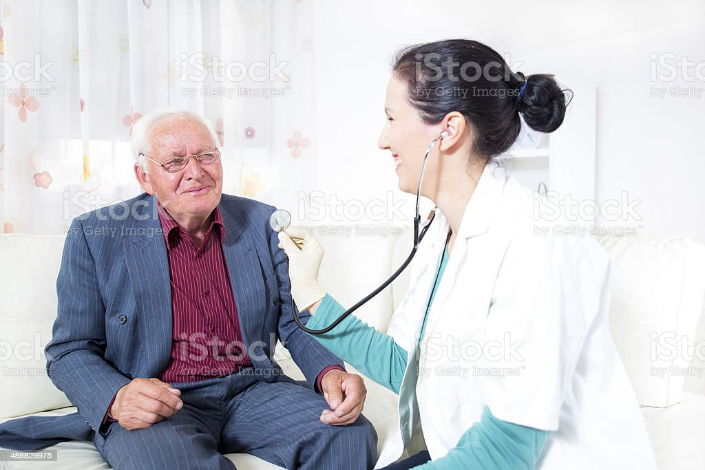 Doctor talking to her male senior patient royalty-free stock photo
