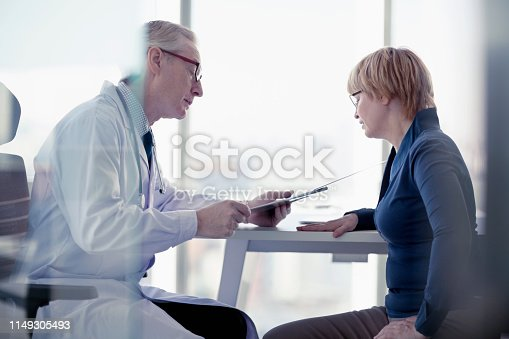 1021670950istockphoto Doctor talking to patient at desk in office 1149305493