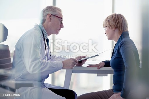 1021670950istockphoto Doctor talking to patient at desk in office 1149305507