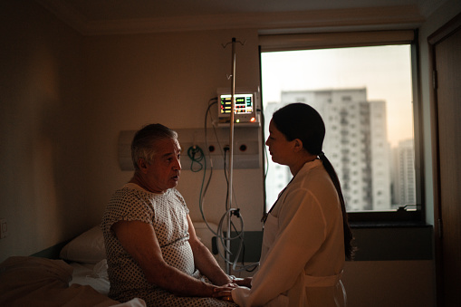 1049772134 istock photo Doctor talking to patient at hospital room 1236342718