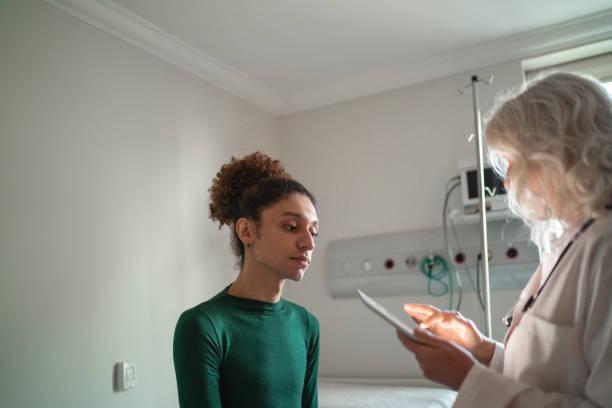"""デジタルタブレットで病室で患者と話す医師 - """"gender fluid"""" ストックフォトと画像"""