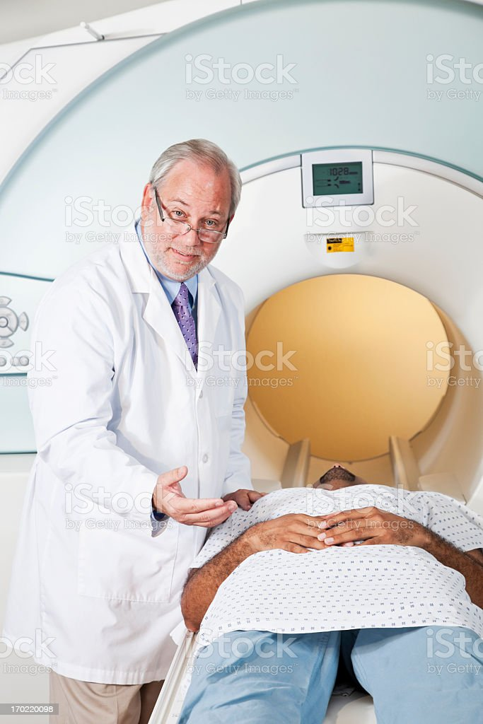 Doctor talking to patient getting MRI scan stock photo