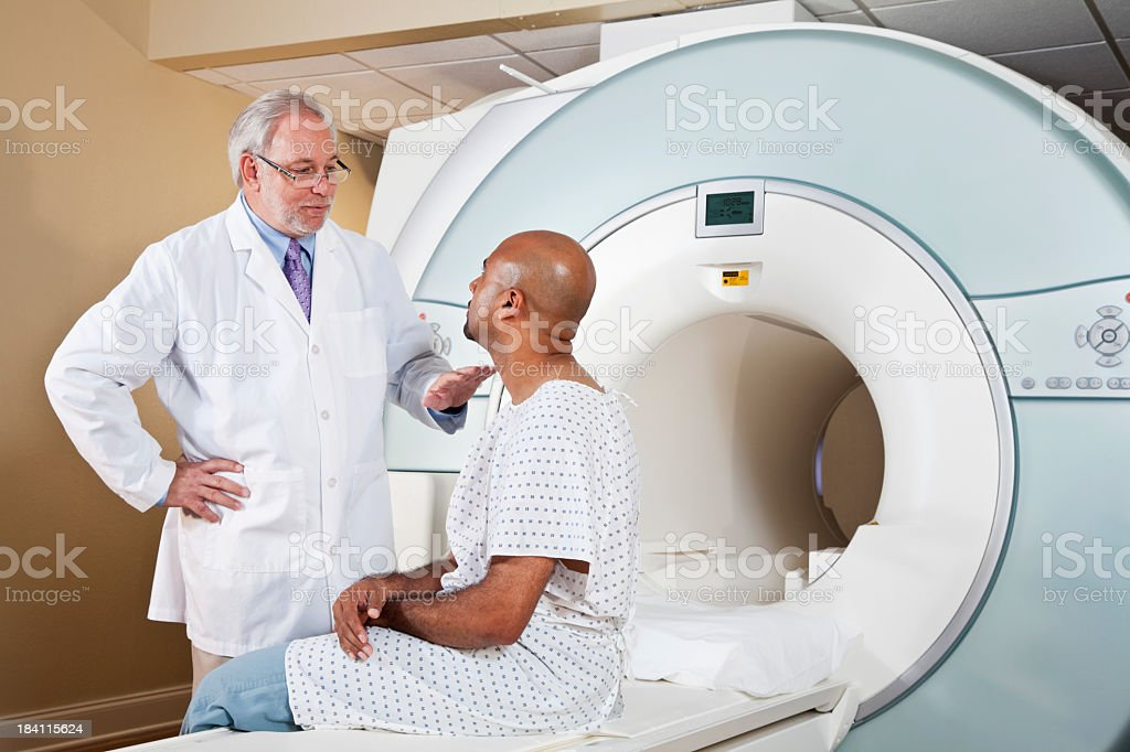Doctor talking to patient getting MRI scan royalty-free stock photo