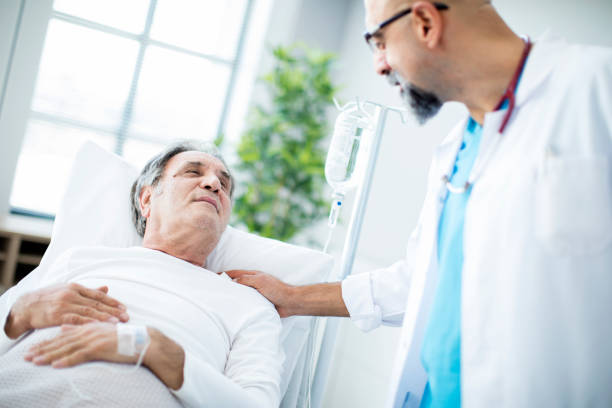 doctor talking to patient in hospital bed - cancer patient stock pictures, royalty-free photos & images