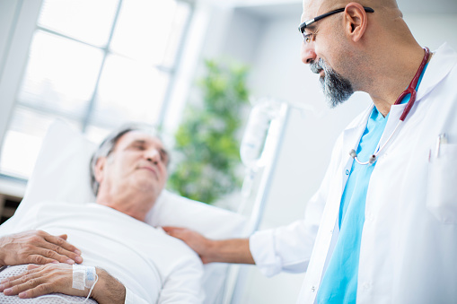 1049772134 istock photo Doctor talking to patient in hospital bed 852092658