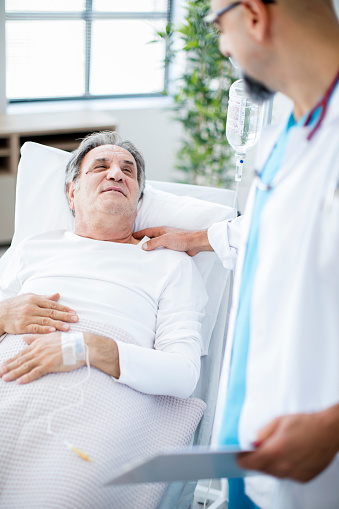 1049772134 istock photo Doctor talking to patient in hospital bed 852092694
