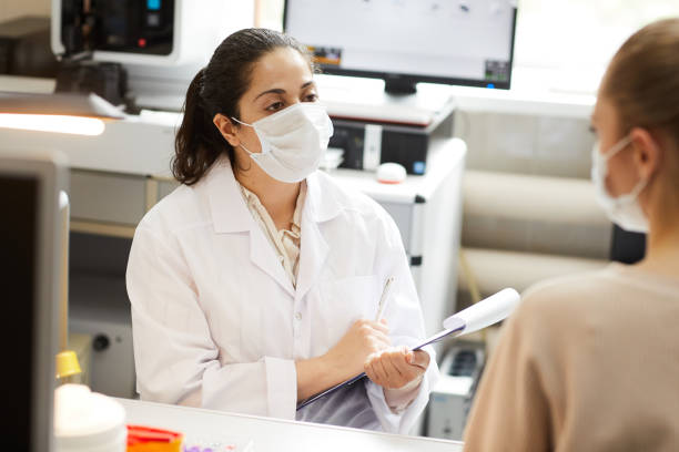 Doctor talking to patient Female doctor in mask making notes in medical card while talking to patient at hospital medical research stock pictures, royalty-free photos & images