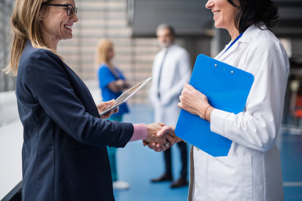 Doctor talking to pharmaceutical sales representative, shaking hands. stock photo