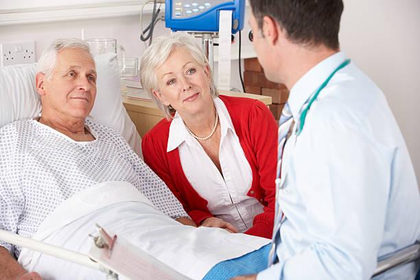 Doctor talking to senior couple on UK Hospital ward stock photo