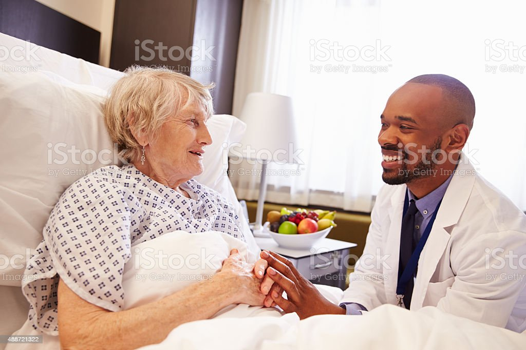 Doctor Talking To Senior Female Patient In Hospital Bed stock photo