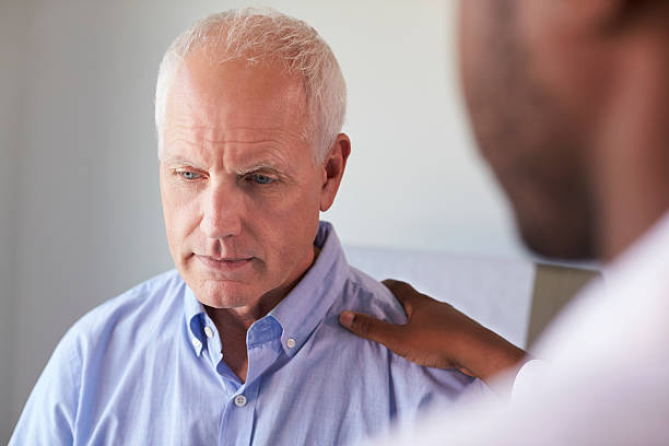 Doctor Talking To Unhappy Male Patient In Exam Room stock photo