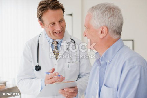 istock Doctor talking with patient in doctors office 107429830