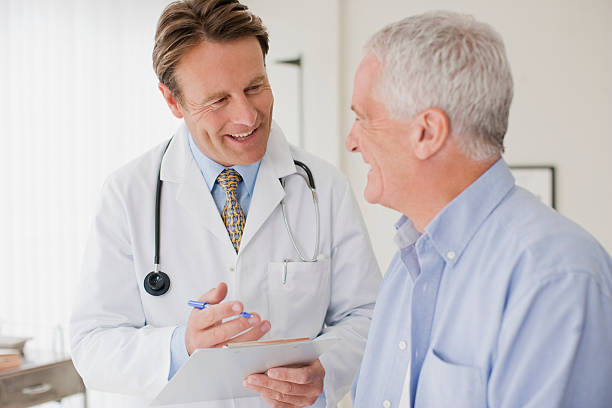 Doctor talking with patient in doctors office stock photo