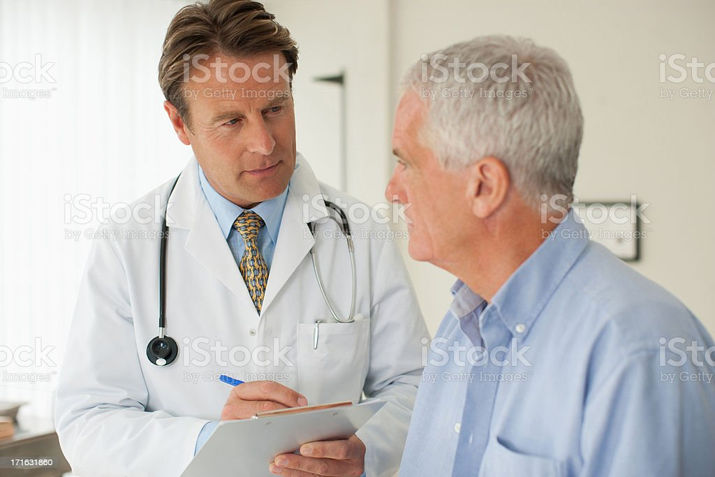 Doctor talking with patient in doctor's office stock photo