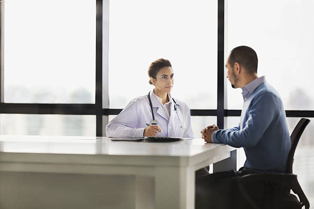 Doctor talking with patient in meeting room stock photo