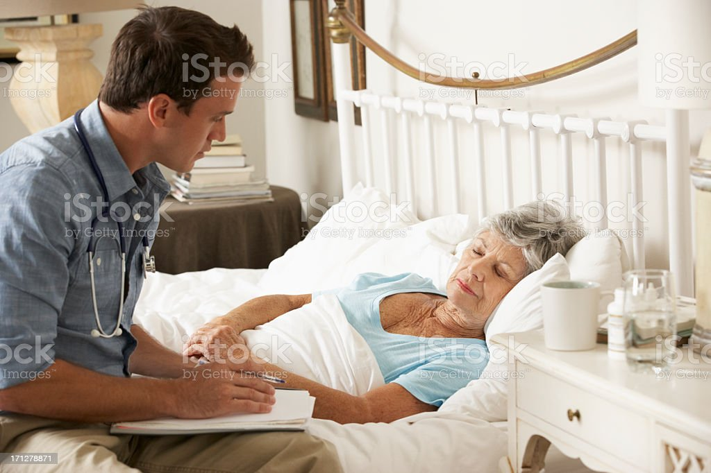 Doctor Talking With Senior Female Patient In Bed At Home royalty-free stock photo